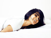 Young pretty tann woman in bed among white sheets having fun, tr Royalty Free Stock Images