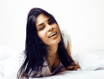 Young pretty tann woman in bed among white sheets having fun, tr Stock Photo