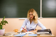 Young pretty teacher checking the tests. Royalty Free Stock Photos