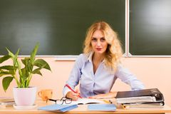 Young pretty teacher checking the tests. Back to school concept Stock Images