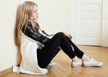 Young pretty teenage blond girl sitting on floor at home despair sad alone, lifestyle concept. In white interior Stock Photography
