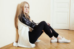 Young pretty teenage blond girl sitting on floor at home despair sad alone, lifestyle concept. In white interior Royalty Free Stock Photo