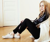 Young pretty teenage blond girl sitting on floor at home despair. Sad alone, lifestyle people concept Stock Photo
