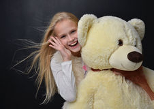 Young pretty teenage girl happy hugging big teddy bear smiling Royalty Free Stock Image