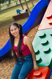 Young pretty teenage girl with pig tails wearing jeans and purple top, sitting on kid latter at outdoors playground Stock Photography