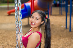 Young pretty teenage girl with pig tails wearing jeans and purple top, sitting on swing at outdoors playground, smiling Stock Images
