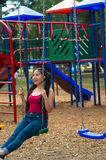Young pretty teenage girl with pig tails wearing jeans and purple top, sitting on swing at outdoors playground, smiling Stock Photo