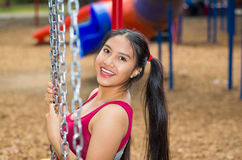 Young pretty teenage girl with pig tails wearing jeans and purple top, sitting on swing at outdoors playground, smiling Royalty Free Stock Photos