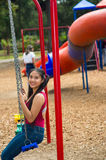 Young pretty teenage girl with pig tails wearing jeans and purple top, sitting on swing at outdoors playground, smiling Royalty Free Stock Photography