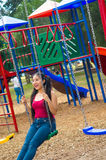 Young pretty teenage girl with pig tails wearing jeans and purple top, sitting on swing at outdoors playground, smiling Royalty Free Stock Image