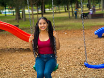 Young pretty teenage girl with pig tails wearing jeans and purple top, sitting on swing at outdoors playground, smiling Stock Photography