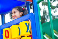 Young pretty teenage girl with pig tails wearing purple top, standing inside plahouse tower smiling happily, playground Royalty Free Stock Photo