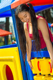 Young pretty teenage girl with pig tails wearing purple top, standing inside plahouse tower smiling happily, playground Stock Photos