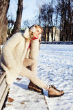 Young pretty teenage hipster girl outdoor in winter snow park having fun drinking coffee, warming up happy smiling Stock Photography