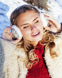 Young pretty teenage hipster girl outdoor in winter snow park having fun drinking coffee, warming up happy smiling Royalty Free Stock Image