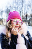 Young pretty teenage hipster girl outdoor in winter snow park having fun drinking coffee, warming up happy smiling Royalty Free Stock Photo