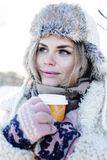 Young pretty teenage hipster girl outdoor in winter snow park having fun drinking coffee, warming up happy smiling Stock Photo