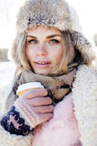 Young pretty teenage hipster girl outdoor in winter snow park having fun drinking coffee, warming up happy smiling Stock Photos