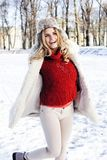 Young pretty teenage hipster girl outdoor in winter snow park having fun drinking coffee, warming up happy smiling Royalty Free Stock Images