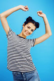 Young pretty teenage modern hipster girl posing emotional happy smiling on blue background, lifestyle people concept Royalty Free Stock Images