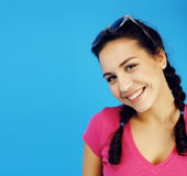 Young pretty teenage modern hipster girl posing emotional happy smiling on blue background, lifestyle people concept Royalty Free Stock Photo