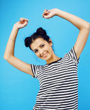 Young pretty teenage modern hipster girl posing emotional happy smiling on blue background, lifestyle people concept Stock Photo