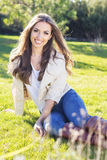 Young pretty teenager girl sitting on green grass Stock Images