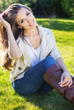 Young pretty teenager girl sitting on green grass Royalty Free Stock Photos