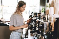 A young pretty thin blonde,dressed in casual outfit,is cooking coffee in a popular coffee shop. royalty free stock photo