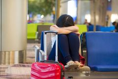 Young pretty tired and exhausted Asian Korean tourist woman in airport sleeping bored sitting at boarding gate hall waiting for de stock photography