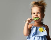 Young pretty toddler girl kid with big  sweet lollypop candy in blue dress on grey. Background Royalty Free Stock Image