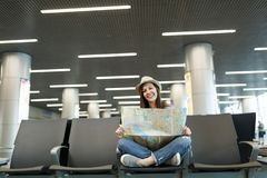 Young pretty traveler tourist woman with crossed legs holding paper map, search route waiting in lobby hall at. International airport. Passenger traveling stock photo