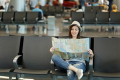 Young pretty traveler tourist woman holding paper map, search route waiting in lobby hall at international airport. Passenger traveling abroad on weekends stock image