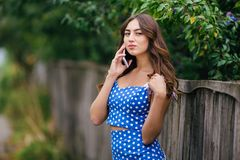 Young pretty trendy smiling girl talking on smart phone in the c stock photo