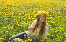 Young pretty woman. In wreath of dandelions in the meadow solar day royalty free stock images