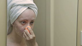 Young, pretty woman applying concealer on her eyelid in bathroom stock video footage