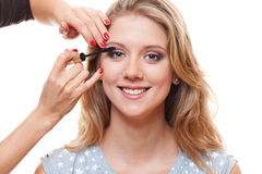 Young pretty woman applying mascara. Portrait of young pretty woman applying mascara over white background Royalty Free Stock Images