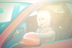 Young pretty woman as driver of red sport car. Portrait of sexy blonde young pretty woman looking from drivers place of red sport tuning car. She has only red Royalty Free Stock Photography