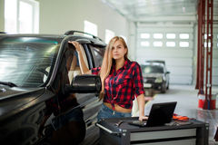 Young pretty woman as a mechanic in checked shirt witch diagnostic system in garage Stock Photos