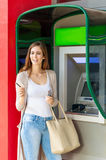 Young pretty woman at the ATM machine Royalty Free Stock Image