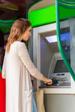 Young pretty woman at the ATM machine Royalty Free Stock Photos