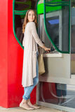 Young pretty woman at the ATM machine Royalty Free Stock Photography