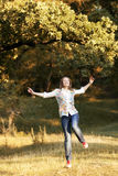 Young pretty woman in the autumn park. Young pretty woman jumping in the autumn park Royalty Free Stock Photos