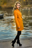 Young pretty woman at the autumn park. With lake on the background stock photo