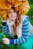 Young pretty woman in the autumn park makes a wreath of leaves Stock Photo