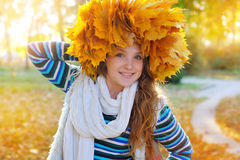 Young pretty woman in the autumn park makes a wreath of leaves Royalty Free Stock Photos