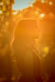 Young pretty woman in the autumn park profile view backlit by sunset headshot Royalty Free Stock Images