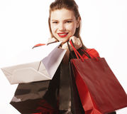 Young pretty woman with bags on Christmas sale in. Red dress isolated white close up Royalty Free Stock Photos