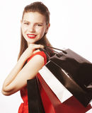Young pretty woman with bags on Christmas sale in. Red dress isolated white close up smiling Royalty Free Stock Images