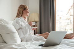 Young pretty woman in bathrobe drinking coffee Stock Photography